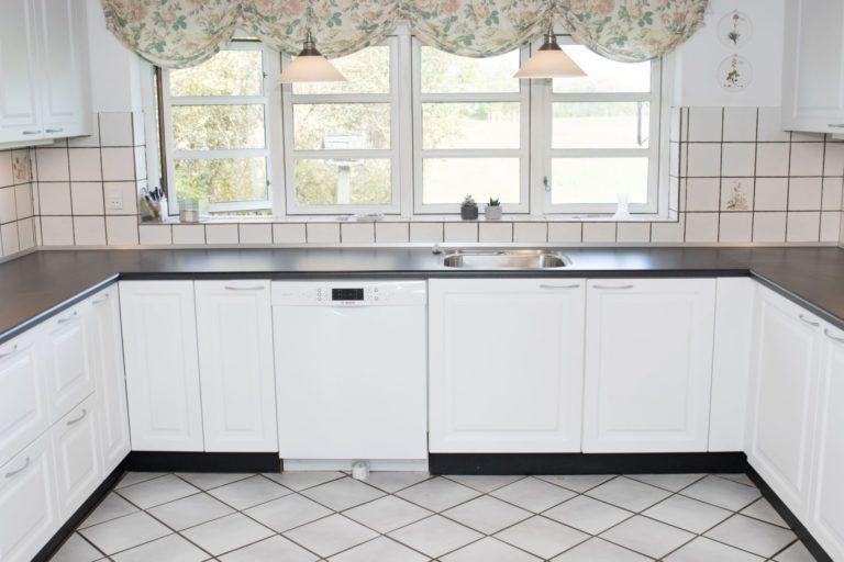 Køkkenfornyelse med nye hvide låger og sort bordplade